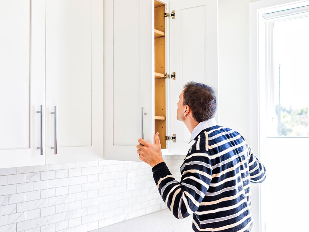 Man looking in kitchen cabinets